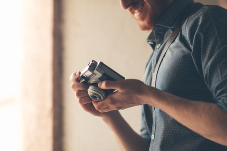 photographer:  young man holding a vintage camera and checking settings