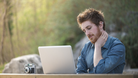 Young hipster man working with his laptop outdoors in nature, trees and plants on background
