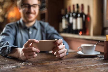 携帯電話を使用してレストランで陽気な男は、手をクローズ アップ 写真素材