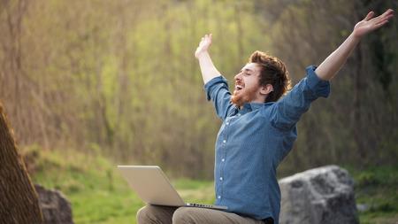 Gelukkig vrolijke man met een laptop zit buiten in de natuur, vrijheid en geluk concept Stockfoto