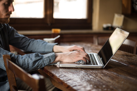 Man working on a laptop on a rustic wooden table next to a window Stock Photo