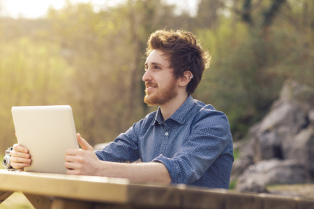 rolledup sleeves: Young smiling hipster man relaxing and having a break at the park and using a laptop Stock Photo