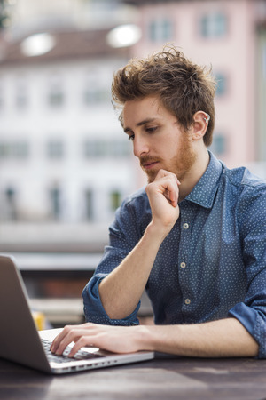 rolledup sleeves: Young  man working with a laptop on an outdoor table with city on background