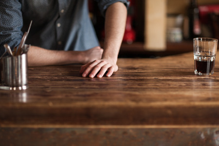 Young barman leaning on wooden bar counter hands close up, unrecognizable person