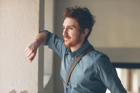 El hombre joven que parece ausente y apoyado en una pared