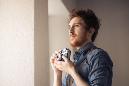 hombre disparando: hombre en busca de un tema interesante para su sesión de fotos y que sostiene una cámara de la vendimia