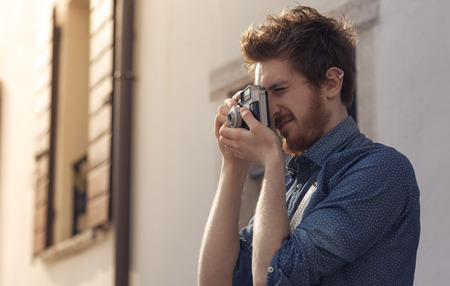 man shooting with an old vintage camera, photography and hobby concept