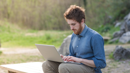 Young  man working on his laptop outdoors in nature, trees and plants on background Stock Photo