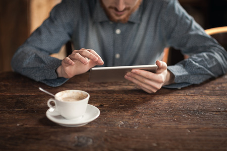 using tablet: Young man using a digital touch screen tablet on a wooden table, hands close up