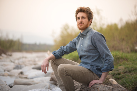 Young  man sitting on rocks next to a river and looking away, nature and healthy lifestyle concept