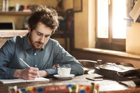 Jonge mens het schetsen op een notebook in zijn atelier op een rustieke houten tafel
