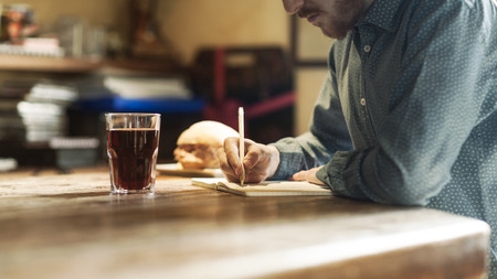 work break: Young hipster man sketching on a  notebook on a rustic wooden table during his lunch break