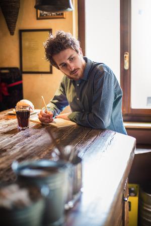to lunch: Hombre joven inconformista dibujar en un bloc de notas en una mesa de madera r�stica durante su hora de almuerzo