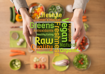 vida sana: Manos que sostienen una tableta de pantalla t�ctil digital con verduras frescas y utensilios de cocina en el fondo y los conceptos de texto alimentarios saludables