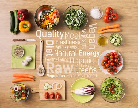 comida: Cozinha vegetariana criativa em casa com legumes frescos saudáveis ??picados, utensílios de cozinha e conceitos de texto alimentação saudável em centro
