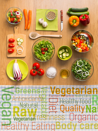 eating utensils: Healthy fresh vegetarian food on kitchen table with healthy eating text concepts on a checked tablecloth, top view Stock Photo
