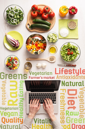 Hands typing on a laptop with fresh vegetables and healthy eating text concepts Reklamní fotografie