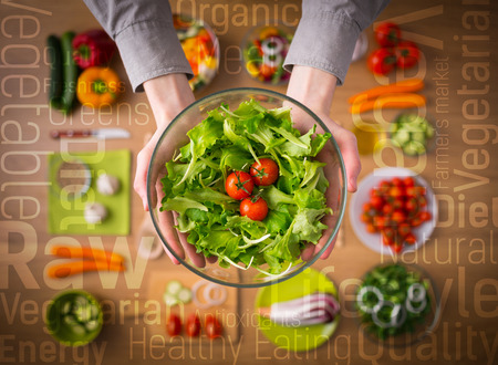 Hands holding an healthy fresh vegetarian salad in a bowl, fresh raw vegetables on background and healthy eating text concepts