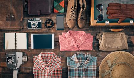 viagem: Hipster acessórios vintage e roupas sobre uma mesa de madeira antes de embalar, viagens e férias conceito, vista de cima