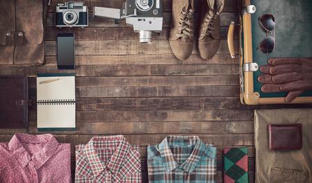 maleta: Vintage embalaje maleta inconformista antes de salir con la maleta vieja, cámara y los accesorios en una mesa de madera, vista desde arriba Foto de archivo