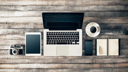 Grunge hippie de bureau en bois avec ordinateur, tablette numérique, appareil photo vintage, téléphone intelligent et portable, vue de dessus