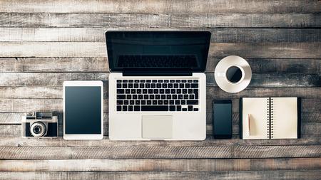 Grunge hipster wooden desktop with computer, digital tablet, vintage camera, smart phone and notebook, top view Standard-Bild