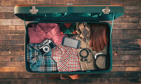 Vintage emballage voyageur de hippie, valise ouverte sur une table en bois avec des vêtements, appareil photo et téléphone mobile, vue de dessus