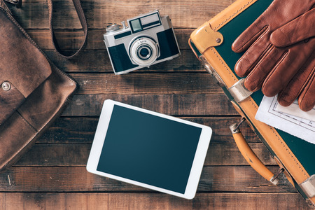 journeys: Vintage hipster traveler packing ready to leave with camera and digital touch screen tablet, top view Stock Photo