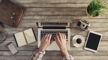 ordinateur bureau: Hipster vue wooden supérieure de bureau, mâle mains taper sur un ordinateur portable Banque d'images