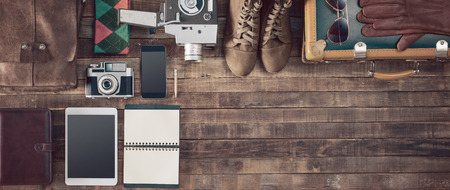 maletas de viaje: Maleta inconformista Vintage embalaje antes de salir con la maleta vieja, cámara, tableta, ropa y accesorios en una mesa de madera, vista desde arriba