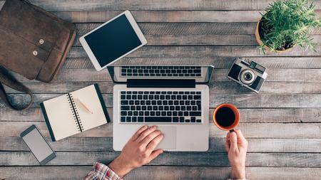 Weinlese-Hippie-Holz Desktop Draufsicht, männliche Hände mit einem Laptop und halten eine Tasse Kaffee