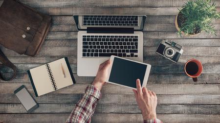 Weinlese-Hippie-Holz Desktop-Ansicht von oben mit Laptop, Vintage-Kamera, Anlagen und Mobil, männliche Hände mit einem digitalen Tablet