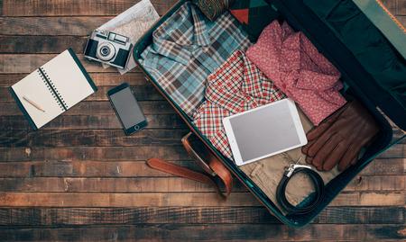 Vintage bederní cestovatel balení, otevřený kufr na dřevěný stůl s oblečením, kamerou a mobilním telefonem, pohled shora