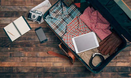 ready: Vintage hipster traveler packing, open suitcase on a wooden table with clothing, camera and mobile phone, top view