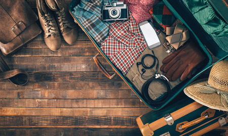 Vintage hipster suitcase packing before leaving with old suitcase, camera and accessories on a wooden table, top view