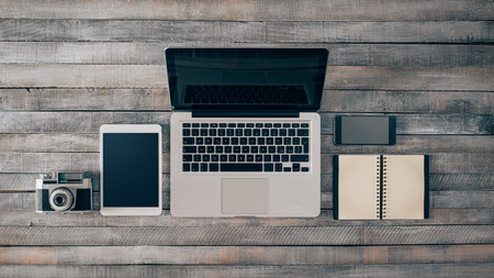 Grunge hipster wooden desktop with computer, digital tablet, vintage camera, smart phone and notebook, top view Banco de Imagens