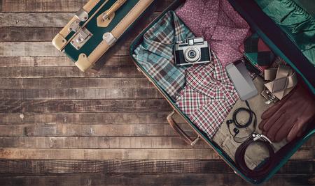 Hipster reiziger vintage klaar koffer met camera en kleding, blanco exemplaar ruimte, bovenaanzicht