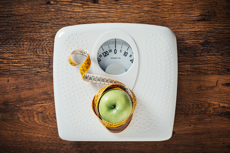 Green apple wrapped in a tape measure on a white scale, wooden surface on background, dieting and weight loss concept Foto de archivo