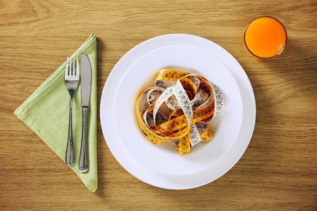 trompo de madera: Conceptos de dieta saludable y pérdida de peso, la tabla describen en una mesa de madera con jugo de frutas y cinta métrica en un plato