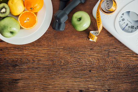 exercise equipment: Fitness and weight loss concept, dumbbells, white scale, fruit and tape measure on a wooden table, top view