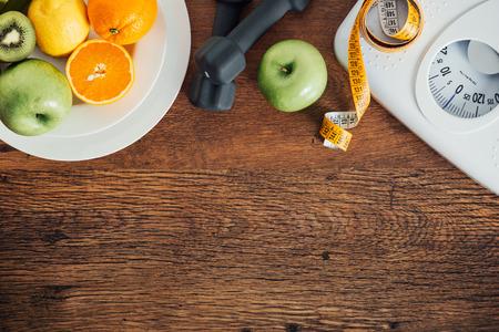fitness: Fitness e perda de peso conceito, halteres, escala branco, frutas e fita métrica em uma mesa de madeira, vista de cima