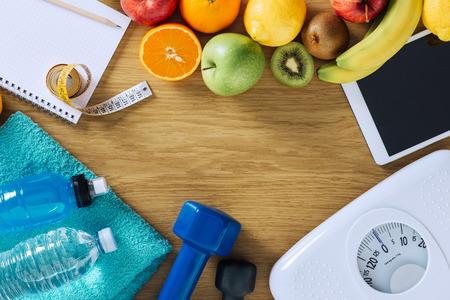 fitnes: Fitness i odchudzanie pojęcie, hantle, biała skala, ręczniki, owoce, taśmy środka i cyfrowy tablet na drewnianym stole, widok z góry
