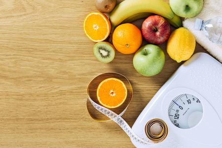 Alimentación saludable, la aptitud y el concepto de pérdida de peso, cinta métrica, la escala blanco y frutas sobre una mesa de madera, espacio de la copia en blanco
