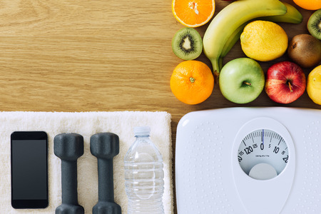 Fitness and weight loss concept, dumbbells, white scale, towel, fruit and mobile phone on a wooden table, top view Stockfoto