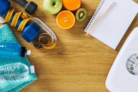 scale weight: Fitness and weight loss concept, dumbbells, white scale, notebook, tape measure and fruit on a wooden table, top view Stock Photo