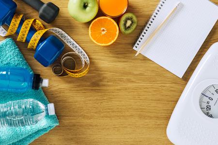 Fitness und Gewichtsverlust Konzept, Hanteln, weiß Skala, Notebook, Maßband und Früchte auf einem Holztisch, Ansicht von oben