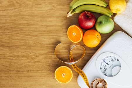 Une saine alimentation, la condition physique et le poids concept de la perte, l'échelle blanc avec des fruits sur une table en bois, espace de copie vierge à gauche