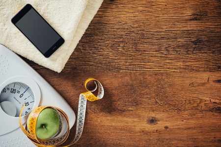 White scale, apple wrapped in a tape measure, towel and smart phone on a wooden table, weight loss and dieting concept