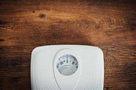 木製テーブル トップ ビュー、フィットネスおよび重量損失の概念上のスケールをホワイト