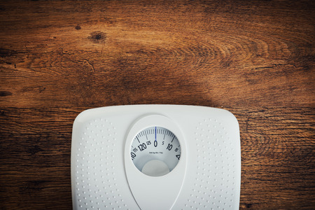 weight control: White scale on a wooden table top view, fitness and weight loss concept